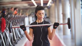 Den unga konditionkvinnaövningen med skivstånger i idrottshallen för byggande tränga sig in lager videofilmer