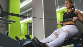 Den unga konditionkvinnan gör övning på roddmaskinen i idrottshall Utbildning för kvinnlig idrottsman nen på exerciseren i vård-  arkivfoto