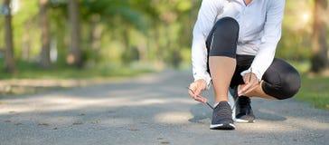 Den unga konditionkvinnan lägger benen på ryggen att gå i den utomhus- kvinnliga löparespringen för parkera på vägen utanför, asi royaltyfri foto