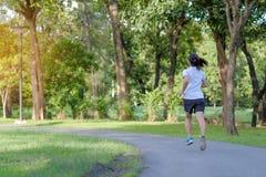 den unga konditionkvinnan som k?r i, parkerar den utomhus- kvinnliga l?paren som utanf?r g?r p? v?gen, asiatiskt jogga f?r idrott royaltyfri bild