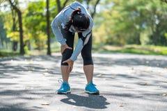 Den unga konditionkvinnan som rymmer hans sportbenskada, tränga sig in smärtsamt under utbildning Asiatisk löpare som har kalvkni arkivfoton