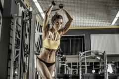 Den unga konditionkvinnan utför övning med övning-maskinen kabel Arkivbild