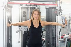 Den unga konditionkvinnan utför övning med övning-maskinen arkivbild