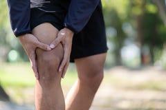 Den unga konditionmannen som rymmer hans sportbenskada, tränga sig in smärtsamt under utbildning Asiatisk löpare som har kalvknip royaltyfria bilder