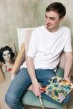 Den unga konstnären kopplar av med målningpaletten royaltyfri fotografi