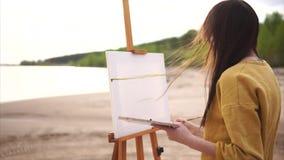 Den unga konstnären målar de första slaglängderna av målarfärg på kanfasen för stilleben arkivfilmer