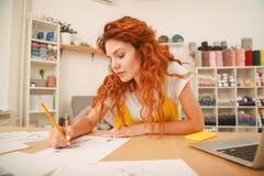Den unga konstnären med ljust rödbrun hår som drar något, skissar Arkivbilder