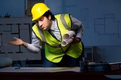 Den unga konstruktionsarkitekten som arbetar på projekt på natten arkivbild