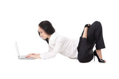 Den unga kontorskvinnan som ligger i yoga, poserar med bärbara datorn, på vitbaksida Royaltyfri Foto