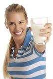 Den unga kvinnadrinken mjölkar Arkivfoton