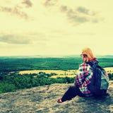Den unga kvinnafotvandraren för blont hår tar en vila på maximumet av berget Arkivfoto