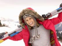 Den unga kvinnaholdingen skidar i alpin liggande Royaltyfri Foto