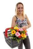 Den unga kvinnan är den hållande korgen med buketten av färgrika blommor Royaltyfria Bilder