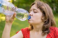 Den unga kvinnan är dricksvatten från flaskan på den soliga varma dagen royaltyfria foton