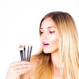 Den unga kvinnan är hållande kosmetiska borstar Smink Arkivbild