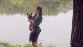 Den unga kvinnan är den hållande orange räven som står vid flodstrand på sommardag lager videofilmer