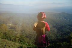 Den unga kvinnan är iklädd infödd kläder som överst står av moun Arkivbilder