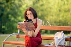 Den unga kvinnan är läseboksammanträde på bänken i staden parkerar under Sunny Warm Weather Royaltyfri Fotografi
