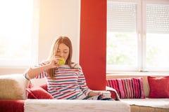 Den unga kvinnan äter äpplet och den läs- tidskriften i vardagsrum royaltyfri bild
