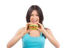 Den unga kvinnan äter den sjukliga hamburgaren för smaklig snabbmat Royaltyfri Foto