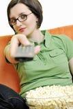 Den unga kvinnan äter popcorn på den orange sofaen Arkivbild