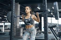 Den unga kvinnan övar i den sunda livsstilen för idrottshallen som drar vikter Arkivbild