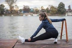 Den unga kvinnan övar vid floden Royaltyfri Fotografi