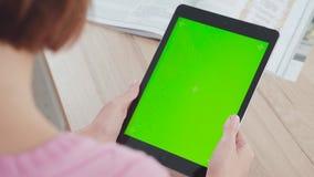 Den unga kvinnan använder en minnestavla med en grön skärm, snirklar, handlag det lager videofilmer
