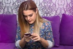 Den unga kvinnan använder en smartphone Arkivbild