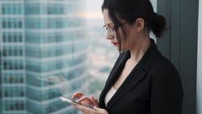 Den unga kvinnan använder en smartphone, medan stå på ett högt golv av en skyskrapa arkivfilmer