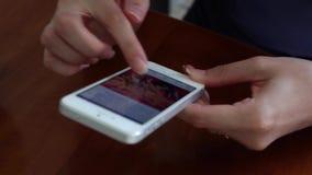Den unga kvinnan använder Facebook app arkivfilmer