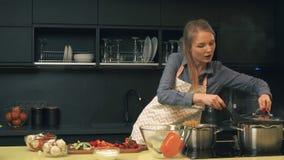 Den unga kvinnan använder smartphonen, medan laga mat arkivfilmer