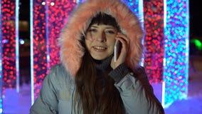 Den unga kvinnan använder telefonen, medan stå bredvid en stor mousserande gåva lager videofilmer