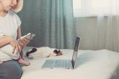 Den unga kvinnan arbetar hemifrån och att rymma behandla som ett barn på varven, katt ligger nära arkivfoton
