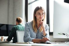 Den unga kvinnan arbetar i regeringsställning genom att använda datoren och den grafiska minnestavlan Royaltyfria Foton
