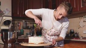 Den unga kvinnan arbetar på kök som förbereder den söta efterrättkakan arkivfilmer