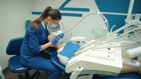 Den unga kvinnan behandlar tänder på tandläkaren stock video