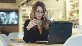Den unga kvinnan betalar för köp på internet vid kreditkorten lager videofilmer