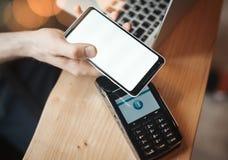 Den unga kvinnan betalar via den betalningterminalen och mobiltelefonen i kafé royaltyfri bild