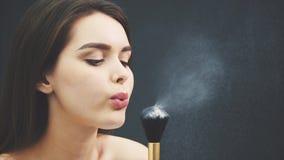 Den unga kvinnan blåser på ett borstepulver för att utgöra makeup Kantjusterad bild Makeupapplikation i närbild Isolerat p? a arkivfilmer