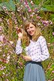 Den unga kvinnan bland de blomstra buskarna av mandeltre-bladet Arkivbilder