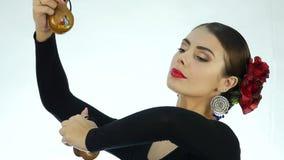 Den unga kvinnan dansar traditionell spanjordans Flamencodansare på en ljus bakgrund långsam rörelse
