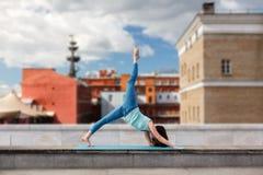 Den unga kvinnan drar ett ben upp främsta stads- byggnader Arkivbild