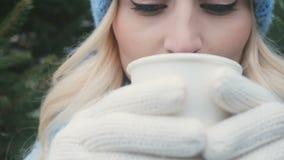 Den unga kvinnan dricker en varm dryck från ett pappers- exponeringsglas arkivfilmer
