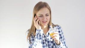 Den unga kvinnan dricker exponeringsglas av orange fruktsaft som talar på smartphonen lager videofilmer