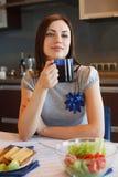 Den unga kvinnan dricker henne morgontea Arkivfoton