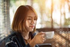 Den unga kvinnan dricker kaffe i coffee shop arkivfoto