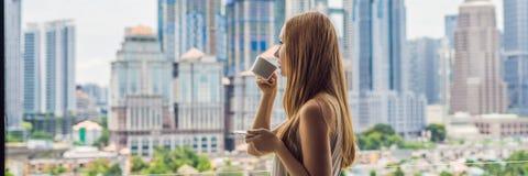 Den unga kvinnan dricker kaffe i morgonen på balkongen som förbiser storstaden och det långa formatet för skyskrapaBANER royaltyfria foton