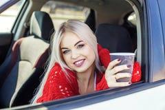 Den unga kvinnan dricker latte i bilen Begreppstur, livsstil, dr fotografering för bildbyråer