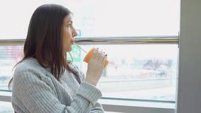 Den unga kvinnan dricker nytt sammanpressad fruktsaft i ett kafé som ut ser fönstret arkivbilder